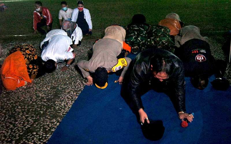 Walikota Tegal Dedy Yon Supriyono (kedua kanan) beserta petugas medis dan TNI Polri melakukan sujud syukur saat Apel penutupan penerapan Pembatasan Sosial Berskala Besar (PSBB) di Alun-alun Kota Tegal, Jawa Tengah, Jumat (22/5/2020) malam. Apel ditandai dengan membunyikan 10 sirine mobil ambulans dan sembilan pemadam kebakaran serta sujud syukur tersebut sebagai tanda berakhirnya penerapan PSBB selama satu bulan di Kota Tegal. ANTARA FOTO/Oky Lukmansyah