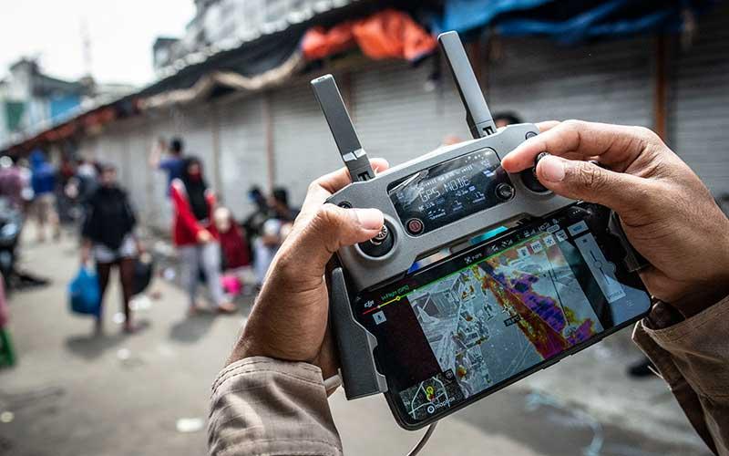 Petugas BNPB menunjukkan hasil perekaman suhu menggunakan drone di kawasan Pasar Tanah Abang, Jakarta, Sabtu (23/5/2020). Pengukuran suhu tubuh di kawasan tersebut bertujuan untuk pencegahan penyebaran COVID-19. ANTARA FOTO/Aprillio Akbar