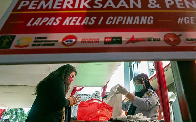Petugas sipir memeriksa barang bawaan keluarga yang akan diberikan kepada warga binaan Lembaga Pemasyarakatan Kelas I Cipinang di Jakarta, Senin (25/5/2020). Kementerian Hukum dan HAM meniadakan kunjungan secara fisik terhadap warga binaan Lapas maupun Rutan saat Hari Raya Idul Fitri 1441 Hijriah untuk mengantisipasi penyebaran COVID-19 dan menggantikannya dengan menyediakan fasilitas komunikasi berbasis panggilan video. ANTARA FOTO/Aditya Pradana Putra