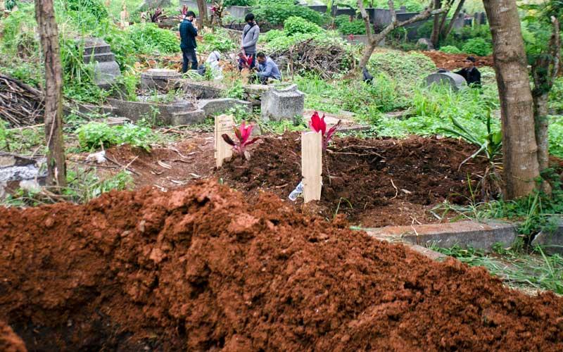Peziarah berdoa di salah satu makam prosedural COVID-19 di TPU Cikadut, Bandung, Jawa Barat, Selasa (26/5/2020). Sejumlah keluarga dan kerabat korban yang dimakamkan sesuai prosedur COVID-19 di TPU terebut mulai terlihat melakukan ziarah kubur pada H+2 Idul Fitri meskipun telah ada imbauan dari Pemerintah untuk tidak melakukan ziarah tradisi lebaran di masa pandemi saat ini. ANTARA FOTO/Novrian Arbi