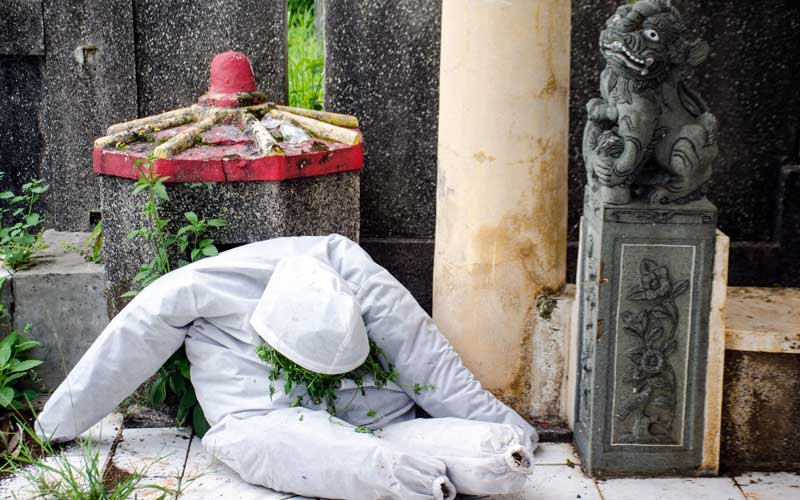 Sebuah pakaian APD COVID-19 tergeletak pada salah satu makam di TPU Cikadut, Bandung, Jawa Barat, Selasa (26/5/2020). Sejumlah keluarga dan kerabat korban yang dimakamkan sesuai prosedur COVID-19 di TPU terebut mulai terlihat melakukan ziarah kubur pada H+2 Idul Fitri meskipun telah ada imbauan dari Pemerintah untuk tidak melakukan ziarah tradisi lebaran di masa pandemi saat ini. ANTARA FOTO/Novrian Arbi