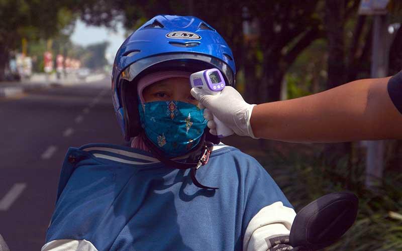 Petugas kesehatan melakukan pemeriksaan suhu tubuh pengendara motor yang melintas di depan pos Keplaksari, Kecamatan Peterongan,Jombang, Jawa Timur, Kamis (28/5/2020). Pemeriksaan tersebut untuk mengantisipasi peningkatan penyebaran virus Corona (COVID-19) di Kabupaten Jombang, karena banyak masyarakat yang sudah mulai kembali beraktivitas di luar rumah. ANTARA FOTO/Syaiful Arif