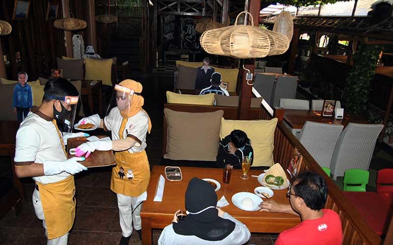 Pelayan menggunakan alat pelindung diri wajah, masker dan sarung tangan saat melayani pelanggan di Rumah Makan Bumi Aki, Pajajaran, Kota Bogor, Jawa Barat, Kamis (28/5/2020). Sejumlah restoran dan rumah makan di Kota Bogor mulai membuka layanan makan di tempat dengan protokol kesehatan ketat setelah penerapan Pembatasan Sosial Berskala Besar (PSBB) Kota Bogor memasuki masa transisi hingga tanggal 4 Juni 2020 guna mengatasi pandemi COVID-19. ANTARA FOTO/Arif Firmansyah