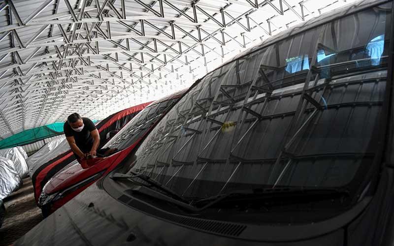Pekerja membersihkan mobil yang digadaikan di gudang penyimpanan kendaraan PT Pegadaian (Persero), Kebon Nanas, Jakarta Timur, Kamis (28/5/2020). PT Pegadaian (Persero) menyatakan permintaan gadai mobil dari nasabah selama pandemi COVID-19 mengalami kenaikan total sebesar 30 persen dari Februari hingga akhir April 2020. ANTARA FOTO/Sigid Kurniawan