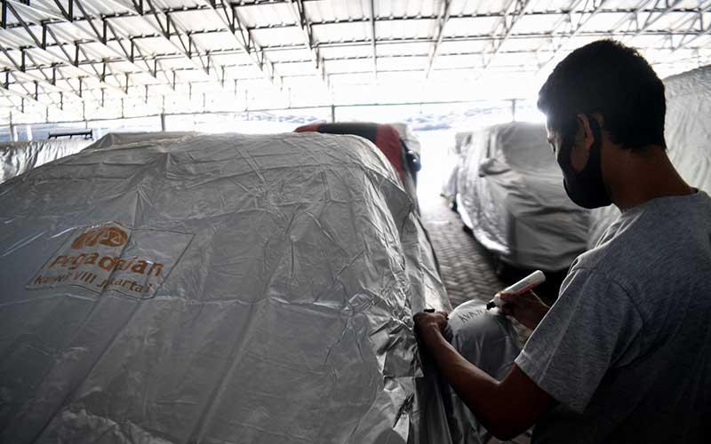 Pekerja mendata mobil yang digadaikan di gudang penyimpanan kendaraan PT Pegadaian (Persero), Kebon Nanas, Jakarta Timur, Kamis (28/5/2020). PT Pegadaian (Persero) menyatakan permintaan gadai mobil dari nasabah selama pandemi COVID-19 mengalami kenaikan total sebesar 30 persen dari Februari hingga akhir April 2020. ANTARA FOTO/Sigid Kurniawan