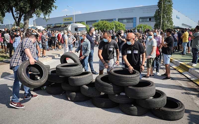 Pekerja membuat blokade dengan ban mobil selama demonstrasi di luar pabrik Nissan Motor Co. di Barcelona, Spanyol, Kamis (28/5/2020). Nissan mengatakan pihaknya berencana menutup pabrik di Barcelona, seiring dengan rencana serupa atas pabriknya di Indonesia. Bloomberg/Angel Garcia