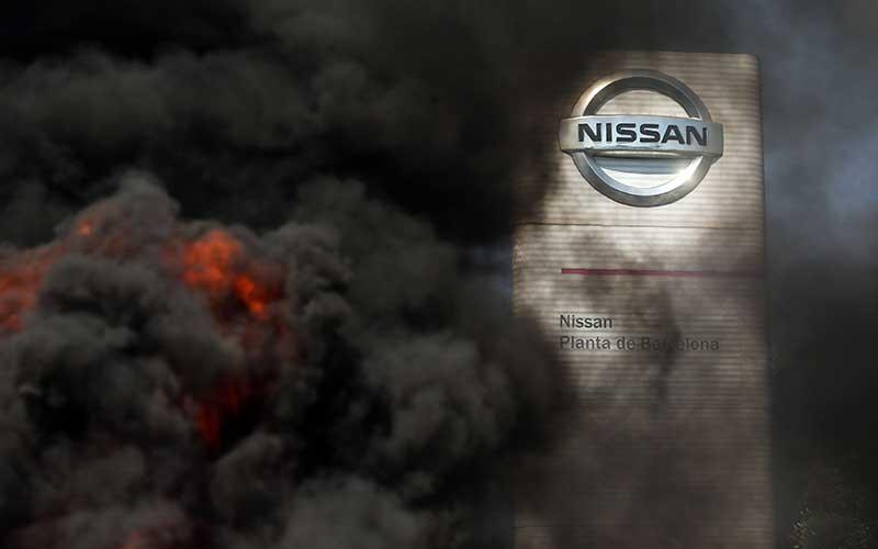 Asap dari ban yang terbakar yang dinyalakan oleh demonstran menutupi logo di luar pabrik Nissan Motor Co. di Barcelona, Spanyol, Kamis (28/5/2020). Nissan mengatakan pihaknya berencana menutup pabrik di Barcelona, seiring dengan rencana serupa atas pabriknya di Indonesia. Bloomberg/Angel Garcia