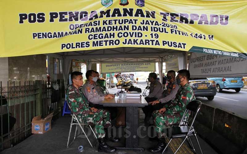 Sejumlah anggota TNI dan polri berjaga di kawasan pasar Tanah Abang, Jakarta, Sabtu (30/5/2020). Kementerian Perdagangan (Kemendag) menerbitkan ketentuan mengenai standar operasional di sektor perdagangan untuk kenormalan baru (new normal), yang tertuang dalam Surat Edaran (SE) No.12/2020 tentang Pemulihan Aktivitas Perdagangan yang Dilakukan Pada Masa Pandemic Corona Virus Disease (Covid-19) dan New Normal. SE ini bertujuan untuk menerapkan protokol kesehatan yang ketat bagi penyelenggaraan kegiatan perdagangan guna memutus mata rantai penularan Covid-19. Bisnis/Arief Hermawan P
