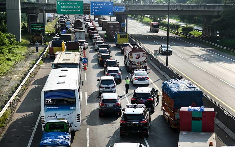 Petugas kepolisian mengatur lalu lintas kendaraan di area pemeriksaan kendaraan yang akan masuk ke wilayah DKI Jakarta di KM 47 Tol Cikampek-Jakarta, Jawa Barat, Sabtu (30/5/2020). Kementerian Perhubungan memprediksi potensi lonjakan arus balik lebaran 2020 akan terjadi pada 30 Mei - 1 Juni, sehingga pengawasan di sejumlah titik pemeriksaan Surat Izin Keluar Masuk (SIKM) akan diperketat. ANTARA FOTO/Muhammad Adimaja