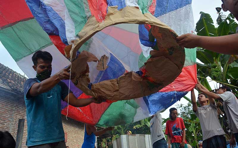 Warga menerbangkan balon udara di Desa Bandung, Kecamatan Diwek, Kabupaten Jombang, Jawa Timur, Minggu (31/5/2020). Meskipun telah dilarang, tradisi menerbangkan balon udara tradisional tetap dilakukan warga di Jombang karena dianggap sudah menjadi tradisi saat perayaan Lebaran Ketupat. ANTARA FOTO/Syaiful Arif