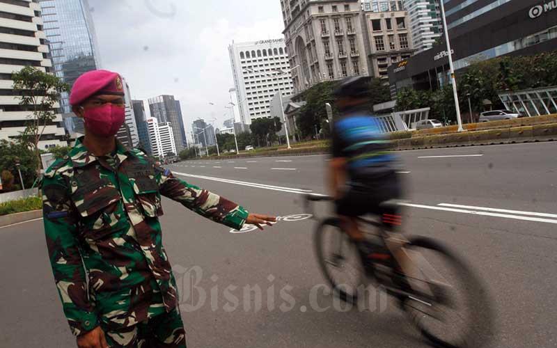 Anggota TNI melakukan penjagaan di kawasan perkantoran dan tempat umum di Jalan Sudirman saat penerapan pembatasan sosial berskala besar (PSBB) di Jakarta, Minggu (31/5/2020). Adapun penjagaan tersebut bertujuan untuk menegakkan disiplin dan protokol kesehatan masyarakat saat pelaksanaan aktivitas normal baru atau new normal di tengah pandemi Covid-19. Bisnis/Himawan L Nugraha