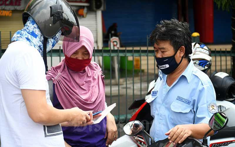 Teknisi ponsel memeriksa handphone warga saat menggelar jasa servis di pinggir jalan raya Cililitan di Jakarta, Senin (1/6/2020). Selama aturan pembatasan sosial berskala besar (PSBB) diberlakukan, pemerintah melarang pusat perbelanjaan buka. Sehingga beberapa pedagang ponsel menjajakan jasanya dipinggir jalan untuk kebutuhan sehari-hari. Bisnis/Abdurachman