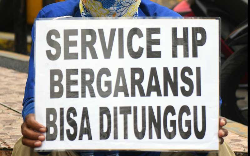 Teknisi ponsel menjajakan jasa servis di pinggir jalan raya Cililitan di Jakarta, Senin (1/6/2020). Selama aturan pembatasan sosial berskala besar (PSBB) diberlakukan, pemerintah melarang pusat perbelanjaan buka. Sehingga beberapa pedagang ponsel menjajakan jasanya dipinggir jalan untuk kebutuhan sehari-hari. Bisnis/Abdurachman