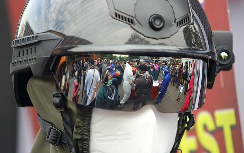 Petugas kesehatan mengenakan alat pelindung diri yang dilengkapi helm pengukur suhu tubuh saat tes diagnostik cepat (rapid test) COVID-19 secara massal di Surabaya, Jawa Timur, Senin (1/6/2020). Tes diagnositk cepat dan swab test yang diselenggarakan oleh Badan Intelijen Negara (BIN) bekerja sama dengan Kementerian Kesehatan dan Pemerintah Kota Surabaya tersebut digelar untuk memetakan kondisi kesehatan masyarakat yang berada di zona merah sekaligus sebagai upaya mencegah penyebaran COVID-19. ANTARA FOTO/Moch Asim