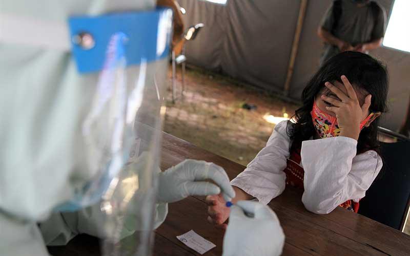 Seorang anak menuntup wajahnya saat tim medis mengambil sampel dalam rapid test gratis di posko gugus tugas COVID-19 di RS Bahteramas Kendari, Kendari, Sulawesi Tenggara, Selasa (2/6/2020). Pihak gugus tugas Sulawesi Tenggara menargetkan rapid test gratis kepada 1.000 orang per hari di Kendari menuju penerapan normal baru dalam upaya pencegahan penyebaran COVID-19. ANTARA FOTO/Jojon