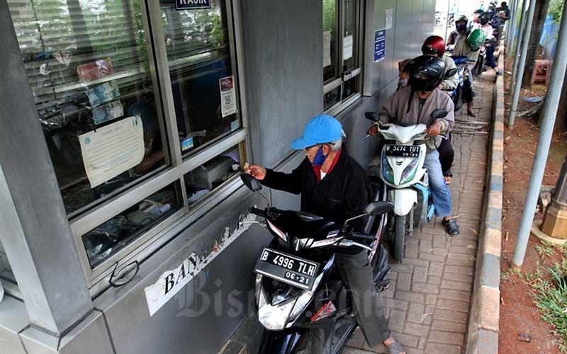 Warga melakukan pembayaran pajak kendaraan bermotor secara drive thru di kantor pelayanan Samsat Jakarta Timur, Jakarta, Selasa (2/6/2020). Polri membuka kembali layanan Satuan Pelayanan Administrasi (Satpas), Sistem Administrasi Manunggal Satu Atap (Samsat), serta kepengurusan Buku Pemilik Kendaraan Bermotor (BPKB), seiring dengan rencana pemerintah dalam menerapkan tatanan kenormalan baru (New Normal) secara bertahap. Dengan dibukanya kembali layanan ini maka ketentuan perpanjangan penutupan Satpas, Samsat, dan BPKB hingga 29 Juni yang diatur dalam surat telegram nomor ST/1473/V/YAN.1.1/2020 dinyatakan tidak berlaku. Bisnis/Arief Hermawan P