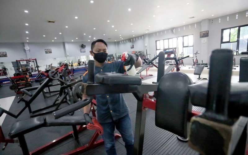 Karyawan membersihkan peralatan olah raga menggunakan cairan desinfektan di salah satu pusat kebugaran di Kota Blitar, Jawa Timur, Selasa (2/6/2020). Menghadapi tatanan normal baru sejumlah tempat kebugaran yang sebelumnya tutup, mulai beroperasi dengan tetap menerapkan protokol kesehatan guna menekan penyebaran COVID-19. ANTARA FOTO/Irfan Anshori