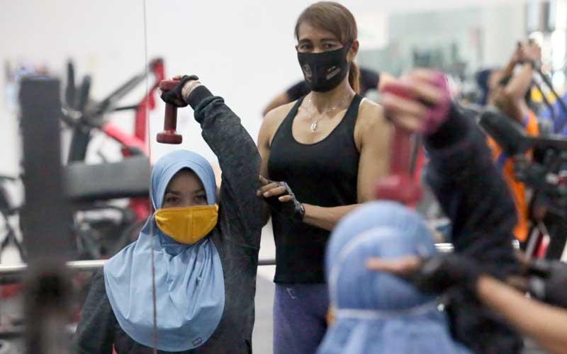 Pengunjung berolah raga angkat beban sambil menggunakan masker di salah satu pusat kebugaran di Kota Blitar, Jawa Timur, Selasa (2/6/2020). Menghadapi tatanan normal baru sejumlah tempat kebugaran yang sebelumnya tutup, mulai beroperasi dengan tetap menerapkan protokol kesehatan guna menekan penyebaran COVID-19. ANTARA FOTO/Irfan Anshori