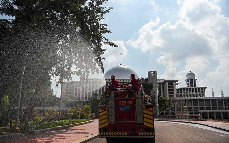 Petugas pemadam kebakaran dan penyelamatan DKI Jakarta menyemprotkan disinfektan di halaman Masjid Istiqlal Jakarta, Rabu (3/6/2020). Penyemprotan tersebut sebagai upaya mencegah penyebaran virus corona (COVID-19) di rumah ibadah jika nantinya kembali dibuka untuk umum saat pemberlakuan tatanan hidup normal baru (new normal). ANTARA FOTO/Nova Wahyudi
