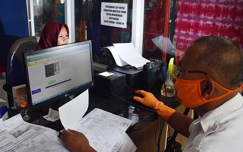 Petugas merekam data pemohon Kartu Tanda Penduduk (KTP) Elektronik di gedung pusat pelayanan publik Pemkab Madiun, Jawa Timur, Rabu (3/6/2020). Dinas Kependudukan dan Pencatatan Sipil setempat membatasi pelayanan permohonan perekaman KTP Elektronik maksimal 20 pemohon per hari karena harus dilakukan dengan protokol kesehatan dalam upaya pencegahan penyebaran Covid-19 antara lain dengan menjaga jarak. ANTARA FOTO/Siswowidodo