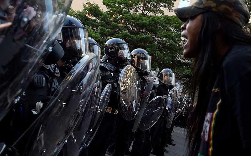 Demonstrans berteriak di depan barisan petugas polisi selama demonstrasi menentang kematian George Floyd di sebuah taman dekat Gedung Putih di Washington, Amerika Serikat, Senin (1/6/2020). Bloomberg/AFP via Getty Images/Olivier Douliery