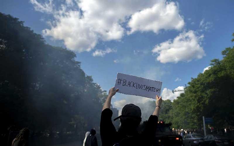 """Demonstrans memegang tulisan """"BLACK LIVES MATTER"""" saat polisi yang menembakkan gas air mata di Philadelphia, Pennsylvania, Amerika Serikat, Senin (1/6/2020). Demonstrasi memprotes kematian George Floyd di Minneapolis, Minnesota saat dalam tahanan polisi seminggu yang lalu telah meluas di seluruh negeri. Bloomberg/Getty Images/Mark Makela"""