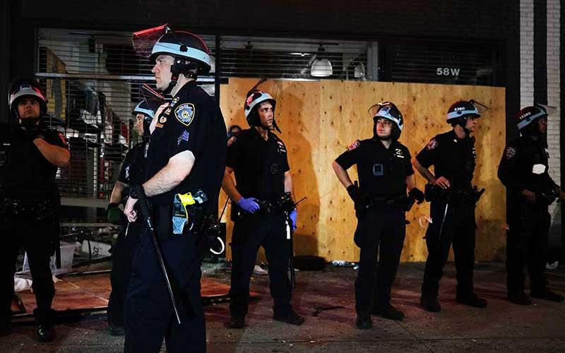 Polisi berjaga di dekat toko-toko yang dijarah pada malam protes atas kematian George Floyd di New York City, Amerika Serikat, Senin (1/6/2020). Bloomberg/Getty Images/Spencer Platt
