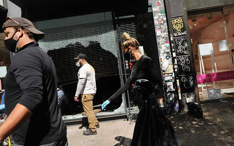 Warga melintas didekat toko yag kacanya pecah dan barangnya di jarah saat malam kerusuhan di Manhattan, New York, Senin (1/6/2020). Bloomberg/ Getty Images/Spencer Platt