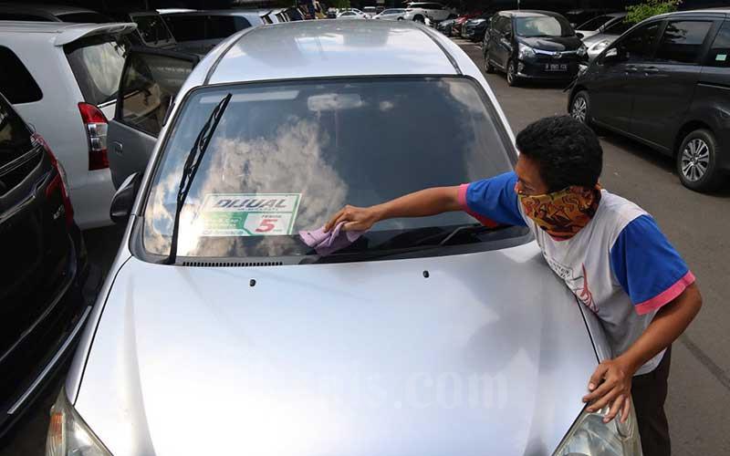 Pekerja membersihkan kendaraan disalah satu gerai mobil bekas di Pasar Mobil Kemayoran, Jakarta, Rabu (3/6/2020). Menurut penjual hampir selama 3 bulan pandemi COVID-19 ini penjualan menurun drastis karena selama pandemi warga lebih memilih berhemat dan mengutamakan kebutuhan primer. Bisnis/Eusebio Chrysnamurti
