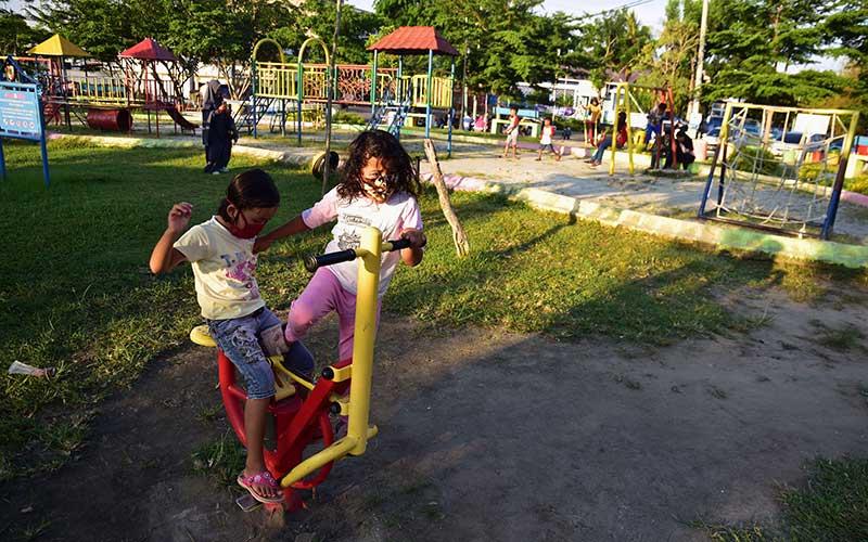 Sejumlah bocah mulai bermain menggunakan fasilitas di taman kota dengan mengenakan masker setelah Pembatasan Sosial Berskala Besar (PSBB) berakhir di Kota Pekanbaru, Riau, Rabu (3/6/2020). Berdasarkan data Dinas Kesehatan Riau, seluruh 36 pasien positif COVID-19 di Kota Pekanbaru sudah dinyatakan sembuh, dan selama 17 hari terakhir tidak ada penambahan kasus baru sehingga pemerintah daerah tak memperpanjang PSBB untuk bersiap melaksanakan tatanan normal baru (new normal). ANTARA FOTO/FB Anggoro/
