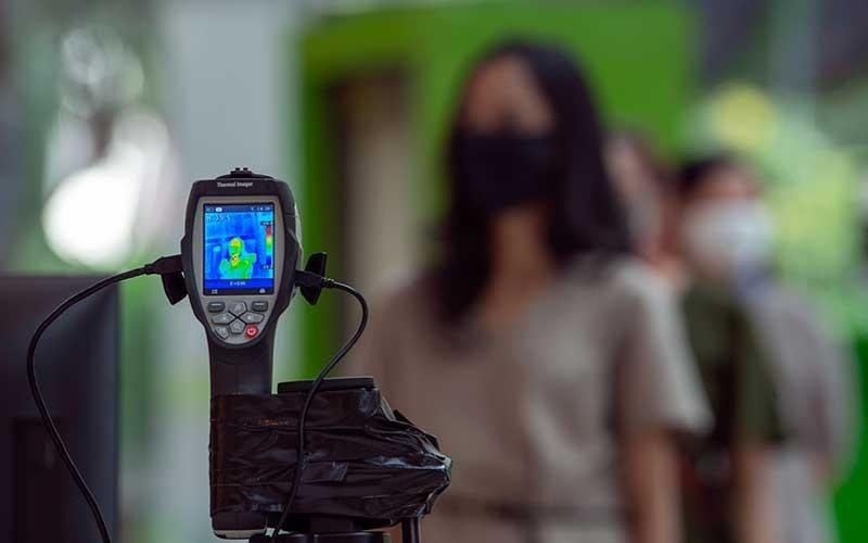 Sejumlah karyawan mengantre untuk mencoba alat pendeteksi suhu tubuh di Mal Central Park, Jakarta, Rabu (3/6/2020). Selain menerapkan protokol kesehatan ketat, sejumlah pusat perbelanjaan juga menyediakan fasilitas pendukung 'physical distancing', seperti mesin pembersih tangan otomatis, mesin penjual masker, alat pendeteksi suhu, dan stiker tanda jaga jarak sebagai persiapan operasional di era normal baru. ANTARA FOTO/Aditya Pradana Putra