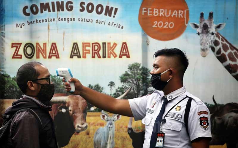 Petugas melakukan thermal scanner kepada awak media yang akan meliput di Bandung Zoological Garden (Bazoga), Bandung, Jawa Barat, Rabu (3/6/2020). Jelang penerapan adaptasi kebiasaan baru (AKB) di Jawa Barat, Bazoga siap terapkan Standar Operational Prosedur (SOP) khusus jika tempat wisata ini kembali dapat izin operasi. SOP tersebut mengatur antara lain jarak antar pengunjung mengantre minimal 1,5 meter, pengunjung wajib menggunakan masker, serta wajib cek suhu tubuh untuk para pengunjung. Bisnis/Rachman