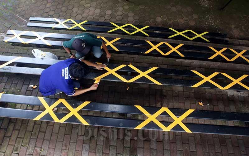 Pekerja menempelkan stiker tanda silang di bangku penonton areal pertunjukan satwa di Bandung Zoological Garden (Bazoga), Bandung, Jawa Barat, Rabu (3/6/2020). Jelang penerapan adaptasi kebiasaan baru (AKB) di Jawa Barat, Bazoga siap terapkan Standar Operational Prosedur (SOP) khusus jika tempat wisata ini kembali dapat izin operasi. SOP tersebut mengatur antara lain jarak antar pengunjung mengantre minimal 1,5 meter, pengunjung wajib menggunakan masker, serta wajib cek suhu tubuh untuk para pengunjung. Bisnis/Rachman