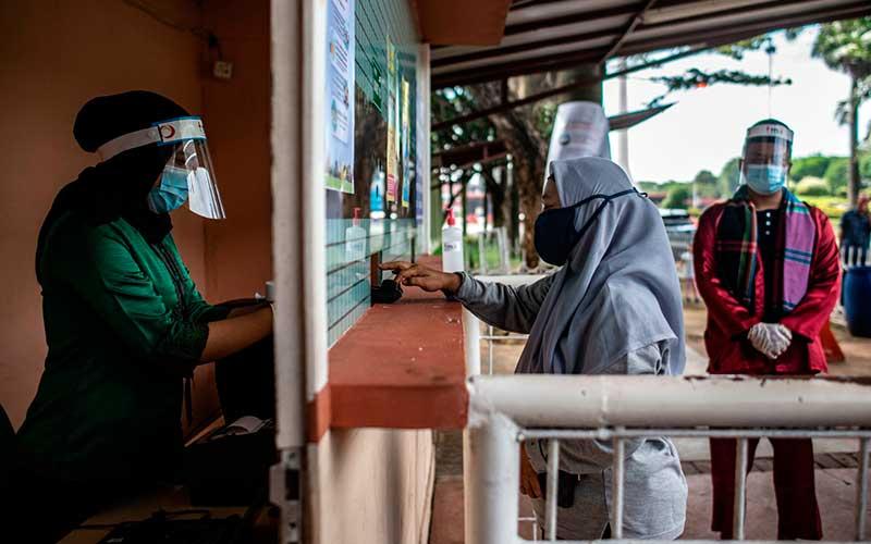 """Petugas melayani wisatawan membeli tiket masuk saat berlangsungnya simulasi normal baru di TMII, Jakarta, Kamis (4/5/2020). Pengelola Taman Mini Indonesia Indah (TMII) telah mempersiapkan penerapan protokol kesehatan saat kehidupan normal baru atau """"new normal"""" diterapkan di DKI Jakarta diantaranya wajib menggunakan masker, pengecekan suhu, menyiapkan klinik kesehatan, menyediakan tempat cuci tangan, dan membatasi jumlah pengunjung hingga 50 persen. ANTARA FOTO/Aprillio Akbar"""