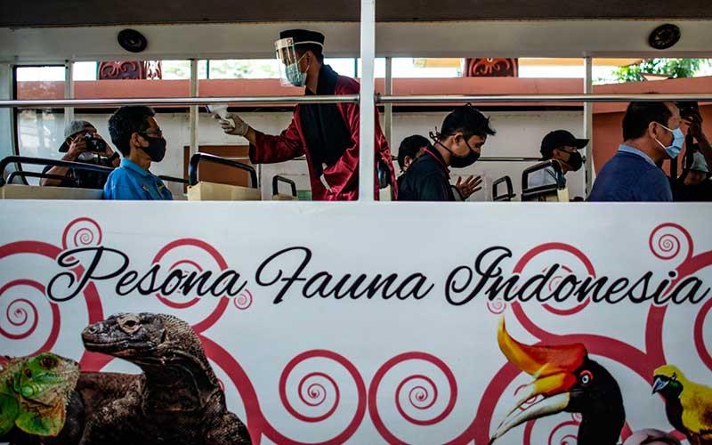 """Petugas mengukur suhu tubuh wisatwan di bus wisata TMII saat berlangsungnya simulasi normal baru di TMII, Jakarta, Kamis (4/5/2020). Pengelola Taman Mini Indonesia Indah (TMII) telah mempersiapkan penerapan protokol kesehatan saat kehidupan normal baru atau """"new normal"""" diterapkan di DKI Jakarta diantaranya wajib menggunakan masker, pengecekan suhu, menyiapkan klinik kesehatan, menyediakan tempat cuci tangan, dan membatasi jumlah pengunjung hingga 50 persen. ANTARA FOTO/Aprillio Akbar"""