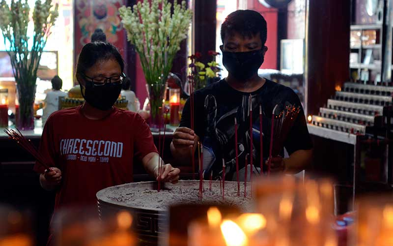 Warga keturunan Tionghoa penganut agama Budha melaksanakan ibadah dengan menggunakan masker pelindung di wajahnya di Vihara Thay Hin Bio, Bandar Lampung, Lampung, Sabtu (6/6/2020). Vihara tersebut mulai ramai dikunjungi umat untuk beribadah dengan menerapkan protokol pencegahan penyebaran Covid-19 menjelang penerapan tatanan hidup normal baru. ANTARA FOTO/Ardiansyah