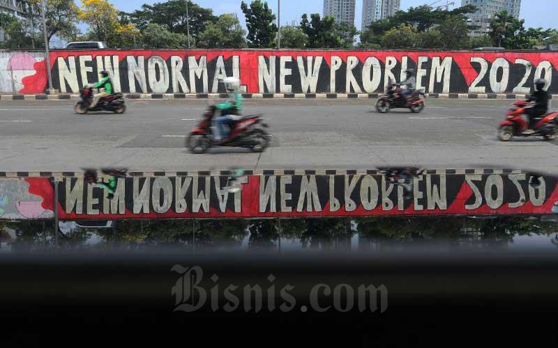 Pengendara roda dua melintas di depan mural New Normal di Jakarta, Sabtu (6/6/2020). Pemprov DKI Jakarta telah menerapkan masa transisi pembatasan sosial berskala besar (PSBB) di DKI Jakarta mulai jumat 5 Juni kemarin. Pada tahap awal ini, sejumlah tempat usaha sudah mulai diperbolehkan beroperasi dengan menerapkan protokol kesehatan. Jadwal PSBB transisi sendiri dibagi menjadi 4 pekan. Pekan pertama adalah tanggal 5-7 Juni, pekan kedua dari 8-14 Juni, pekan ketiga berlangsung sejak 15-21 Juni dan pekan terakhir 22-28 Juni. Bisnis/Abdurachman