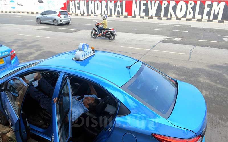 Sopir taksi tidur di dalam mobilnya yang berada di depan mural New Normal di Jakarta, Sabtu (6/6/2020). Pemprov DKI Jakarta telah menerapkan masa transisi pembatasan sosial berskala besar (PSBB) di DKI Jakarta mulai jumat 5 Juni kemarin. Pada tahap awal ini, sejumlah tempat usaha sudah mulai diperbolehkan beroperasi dengan menerapkan protokol kesehatan. Jadwal PSBB transisi sendiri dibagi menjadi 4 pekan. Pekan pertama adalah tanggal 5-7 Juni, pekan kedua dari 8-14 Juni, pekan ketiga berlangsung sejak 15-21 Juni dan pekan terakhir 22-28 Juni. Bisnis/Abdurachman