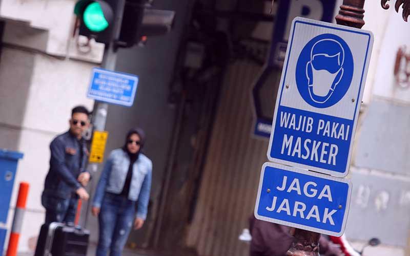 "Rambu ""Wajib Pakai Masker"" dan ""Jaga Jarak"" terpasang di tiang lampu di Jalan Tunjungan, Surabaya, Jawa Timur, Sabtu (6/6/2020). Pemerintah Kota Surabaya memasang rambu-rambu bertuliskan Wajib Pakai Masker dan Jaga Jarak itu di sejumlah ruas jalan dan tempat kumpul warga untuk meningkatkan kesadaran warga mematuhi protokol kesehatan pencegahan penularan Covid-19. ANTARA FOTO/Didik Suhartono"