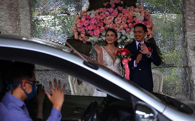 "Pasangan mempelai mengikuti simulasi resepsi pernikahan secara ""drive thru"" di Hotel Istana Nelayan, Kota Tangerang, Banten, Senin (29/6/2020). Hotel tersebut kembali membuka paket resepsi pernikahan di tengah pandemi dengan menggunakan sistem ""drive thru"" guna mencegah penularan Covid-19. ANTARA FOTO/Fauzan"