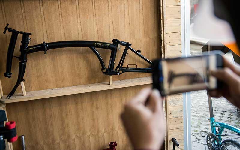 Pengunjung memotret rangka (frameset) sepeda lipat Kreuz di Bandung, Jawa Barat, Senin (29/6/2020). Sepeda lipat Kreuz dengan model yang terinspirasi merk sepeda Brompton ini merupakan karya dari sejumlah pemuda Bandung. Workshop UMKM sepeda lipat Kreuz tersebut mampu memproduksi frameset sebanyak 10-15 buah per bulannya dengan harga jual Rp3,5 juta dan antrean pemesanannya hingga Mei 2022. ANTARA FOTO/M Agung Rajasa