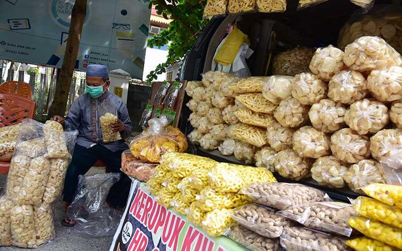 Seorang pedagang mengemas kerupuk kulit dagangannya di mobil sekaligus kios berjalan di Kota Pekanbaru, Riau, Selasa (30/6/2020). Berdasarkan data Ditjen Pajak hingga April 2020 sudah ada 200 ribu usaha mikro kecil dan menengah (UMKM) yang menggunakan insentif pajak penghasilan (Pph) final ditanggung pemerintah, yang diberikan untuk memulihkan bisnis pelaku usaha di tengah wabah Covid-19, namun jumlah itu baru sebagian kecil dari total 67 juta UMKM di Indonesia. ANTARA FOTO/FB Anggoro