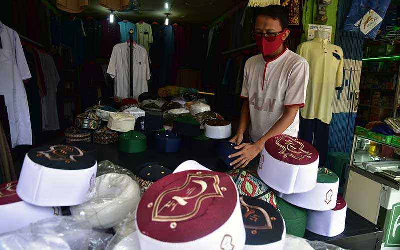 Seorang pedagang menata kopiah di sebuah toko busana muslim di Kota Pekanbaru, Riau, Selasa (30/6/2020). Berdasarkan data Ditjen Pajak hingga April 2020 sudah ada 200 ribu usaha mikro kecil dan menengah (UMKM) yang menggunakan insentif pajak penghasilan (Pph) final ditanggung pemerintah, yang diberikan untuk memulihkan bisnis pelaku usaha di tengah wabah Covid-19, namun jumlah itu baru sebagian kecil dari total 67 juta UMKM di Indonesia. ANTARA FOTO/FB Anggoro