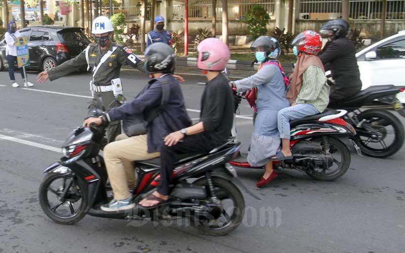 Petugas gabungan melakukan razia pengendara sepeda motor yang tidak menggunakan masker di Makassar, Sulawesi Selatan, Selasa (30/6/2020). Sejumlah pengendara terjaring dalam razia tersebut diberi surat teguraan dan penyataan tidak akan mengulangi lagi. Bisnis/Paulus Tandi Bone