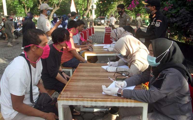 Petugas mendata pelanggar yang mengendarai roda dua tanpa memakai masker yang terjaring razia di Makassar, Sulawesi Selatan, Selasa (30/6/2020). Sejumlah pengendara terjaring dalam razia tersebut diberi surat teguraan dan penyataan tidak akan mengulangi lagi. Bisnis/Paulus Tandi Bone