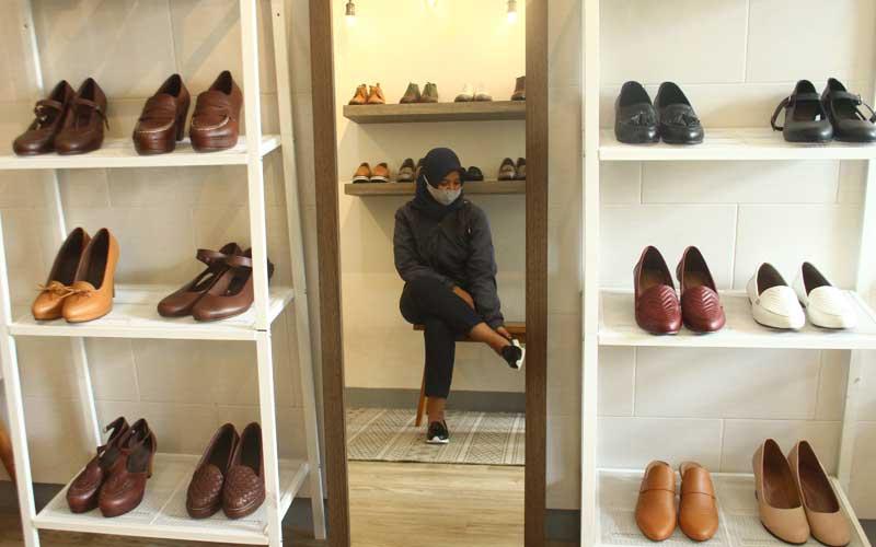 Calon pembeli mencoba mengenakan sepatu kulit kualitas ekspor yang dipajang di rumah produksi Shoeka Shoes di Malang, Jawa Timur, Selasa (30/6/2020). Pengusaha sepatu kulit ekspor setempat mengaku mengandalkan pemasaran digital serta berinovasi membuat produk baru yang murah dan disukai konsumen untuk mengatasi anjloknya permintaan dari seribu pasang menjadi enam ratus pasang per bulan atau menurun 40 persen akibat pandemi Covid-19. ANTARA FOTO/Ari Bowo Sucipto