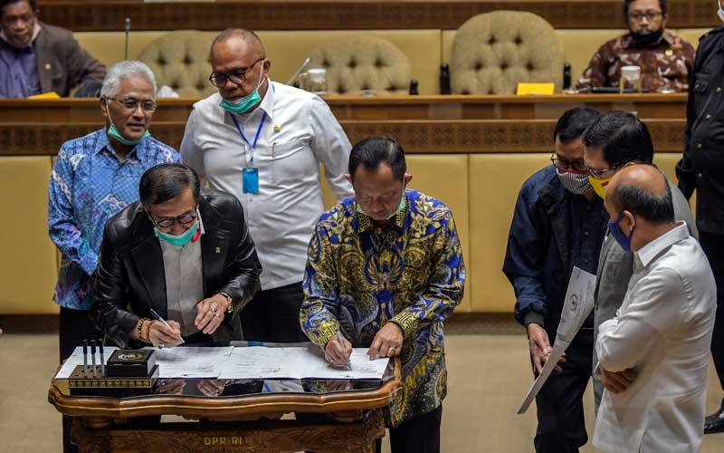 Menteri Hukum dan HAM Yasonna Laoly (kedua kiri) bersama Menteri Dalam Negeri Tito Karnavian (kempat kiri) disaksikan anggota Komisi II DPR menandatangani draf Perppu tentang pilkada usai mengikuti rapat kerja dengan Komisi II DPR di Kompleks Parlemen Senayan, Jakarta, Selasa (30/6/2020). Rapat tersebut menyetujui Perppu Nomor 2 Tahun 2020 tentang Perubahan Ketiga atas Undang-undang Nomor 1 Tahun 2015 tentang Penetapan Peraturan Pemerintah Pengganti Undang-Undang Nomor 1 Tahun 2014 tentang Pemilihan Gubernur, Bupati, dan Wali kota menjadi Undang-Undang dan disahkan dalam rapat paripurna. ANTARA FOTO/Galih Pradipta
