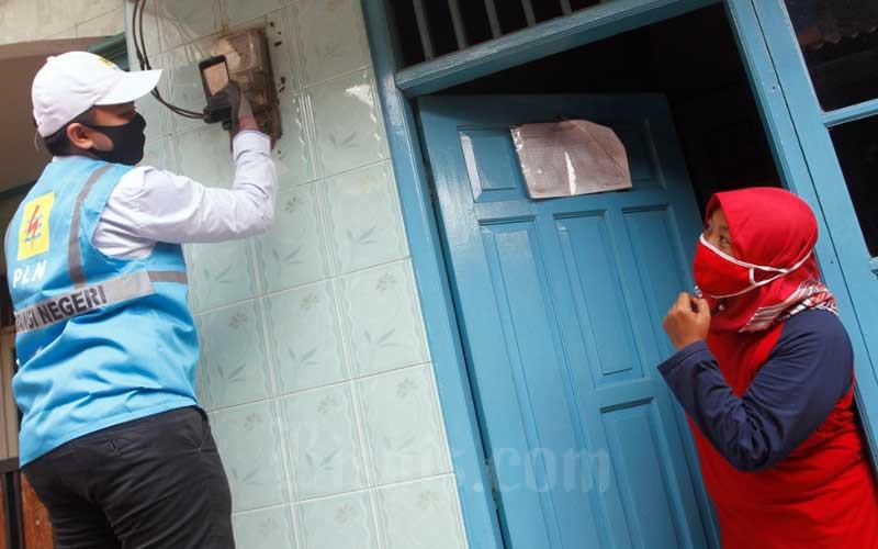 Petugas PLN melakukan pencatatan meteran listrik di salah satu rumah warga di kawasan Cipulir, Jakarta, Selasa (30/6/2020). PT PLN (Persero) memastikan seluruh petugasnya akan melakukan pencatatan meter secara langsung ke rumah pelanggan pascabayar dan tetap memperhatikan protokol pencegahan Covid-19. Hal tersebut guna memastikan kesesuaian tagihan rekening listrik dengan penggunaan listrik oleh pelanggan. Bisnis/Himawan L Nugraha