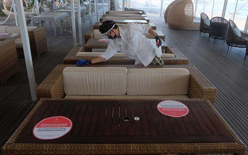 Pekerja menggunakan alat pelindung diri saat membersihkan meja makan bagi wisatawan di Hotel Puri Santrian, Sanur, Denpasar, Bali, Kamis (2/7/2020). ANTARA FOTO/Nyoman Hendra Wibowo