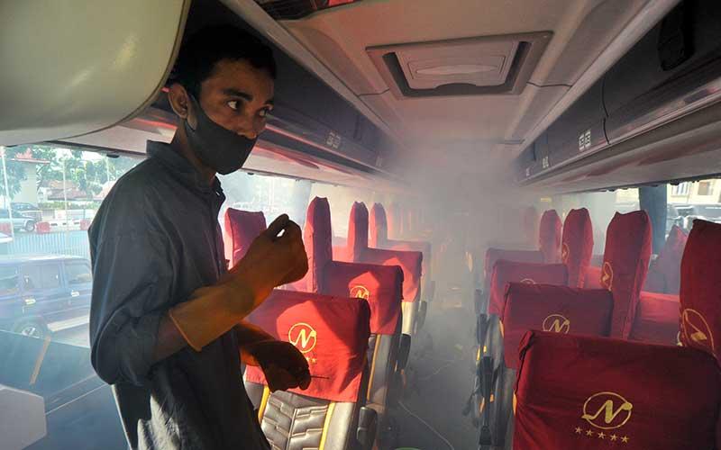 Petugas melakukan sterilisasi bagian dalam bus tujuan Jakarta dengan pengasapan (fogging) disinfektan, di pool PT NPM Padang, Sumatera Barat, Sabtu (4/7/2020). ANTARA FOTO/Iggoy el Fitra